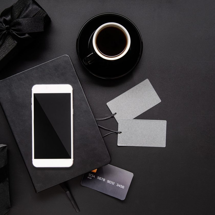 black-smartphone-price-tags-coffee-and-gifts-top-view-on-black-background.jpg